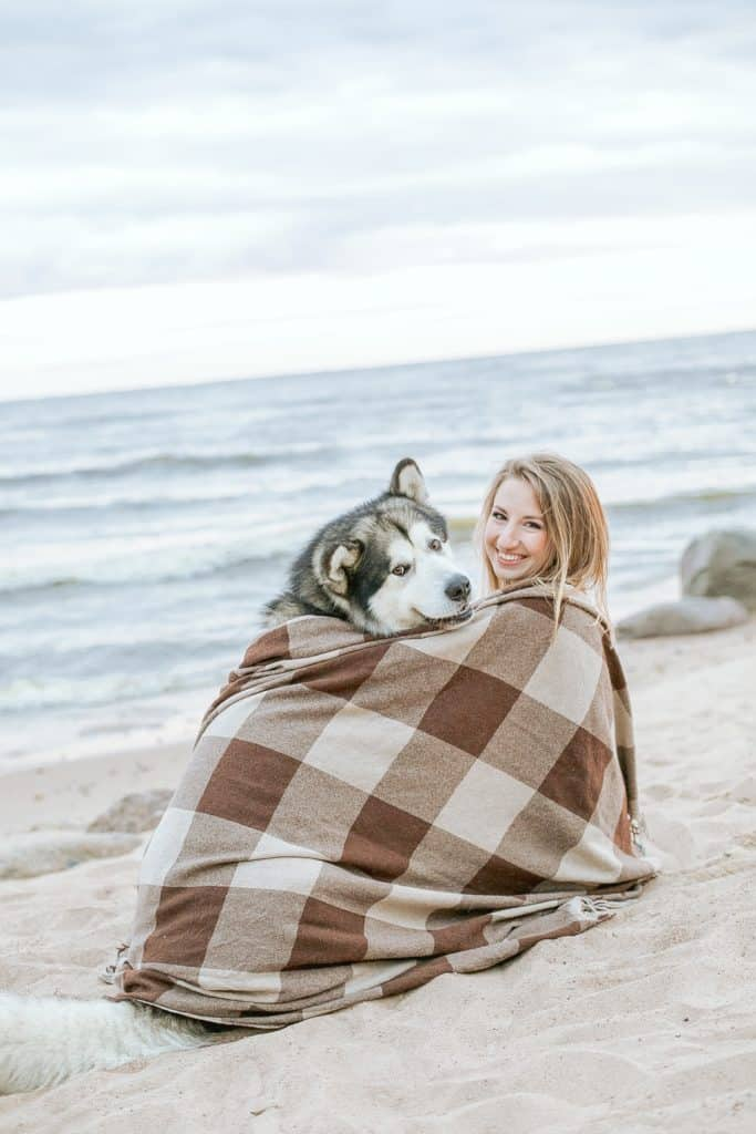 Woman on the beach wrapped in a blanket with dog