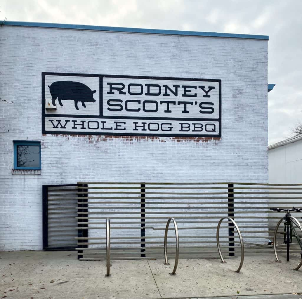 Outside of a barbeque building in Charleston displaying restaurant name, Rodney Scott